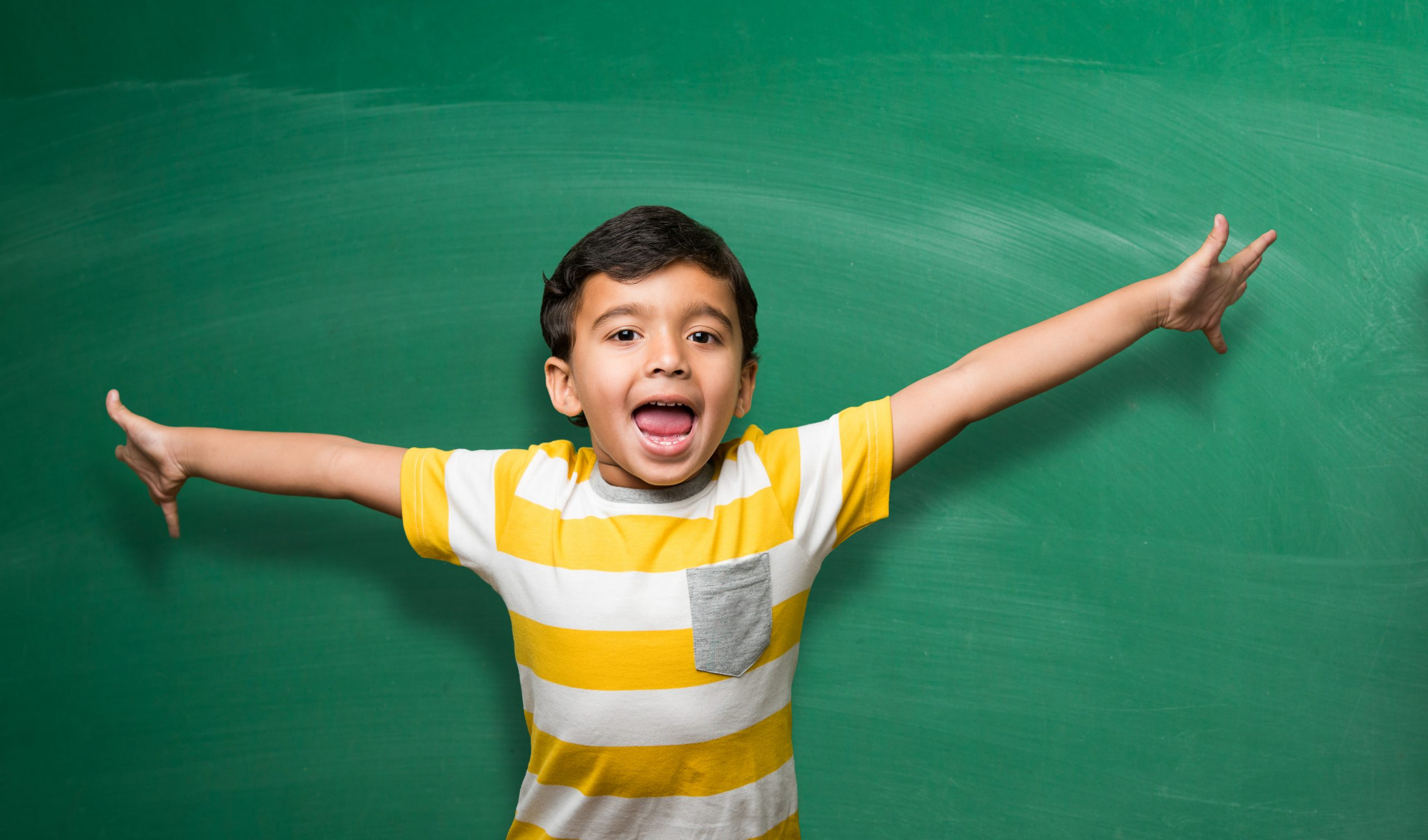 Cute little Indian school kid boy in hand stretched pose over green chalkboard or chalk board background holding books, victory cup etc, isolated
